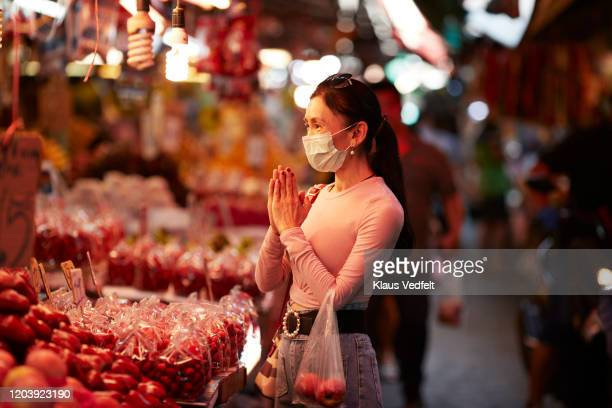 woman with pollution mask greeting at market stall - china coronavirus stock pictures, royalty-free photos & images