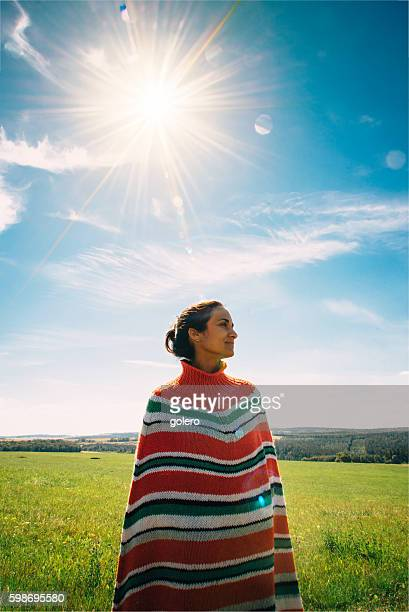 woman with poncho in summer landscape at early summer morning