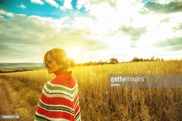 woman with poncho in summer landscape at sunset hour