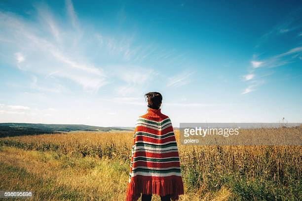 woman with poncho looking over late summer landscape