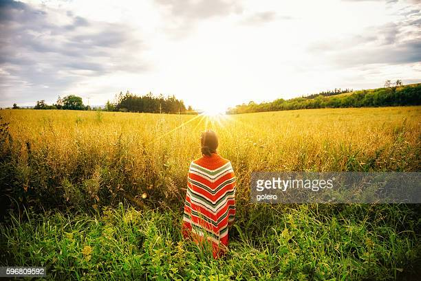 woman with poncho standing in summer field