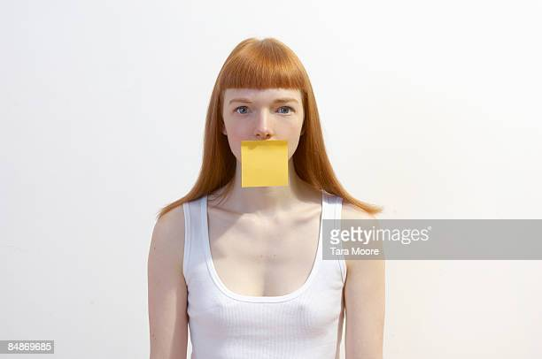 woman with post-it note covering mouth