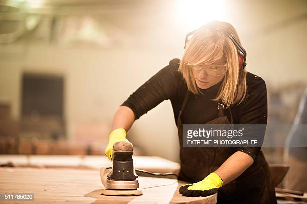 Woman with power sander at work