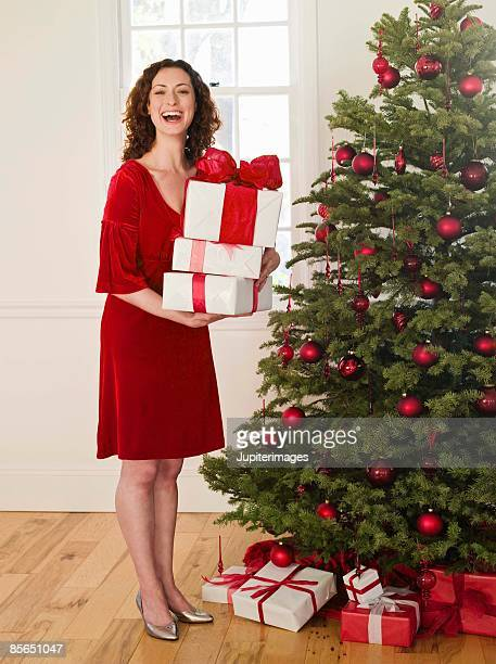 woman with presents and christmas tree - mid adult stock pictures, royalty-free photos & images