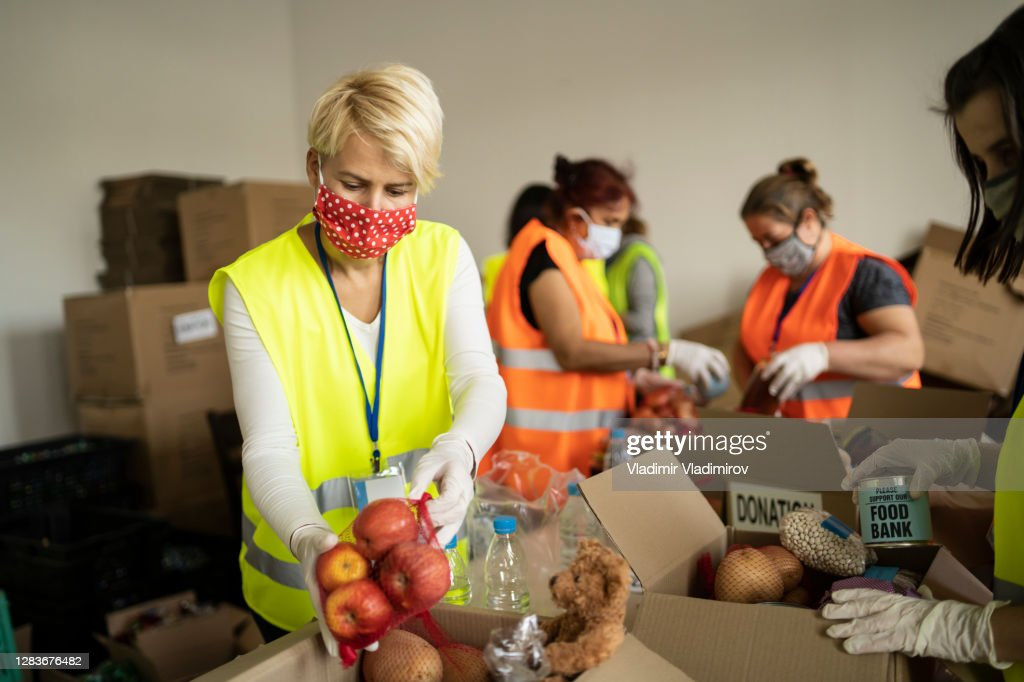 Woman with protective face mask helping collecting food in a homeless shelter : Stock Photo