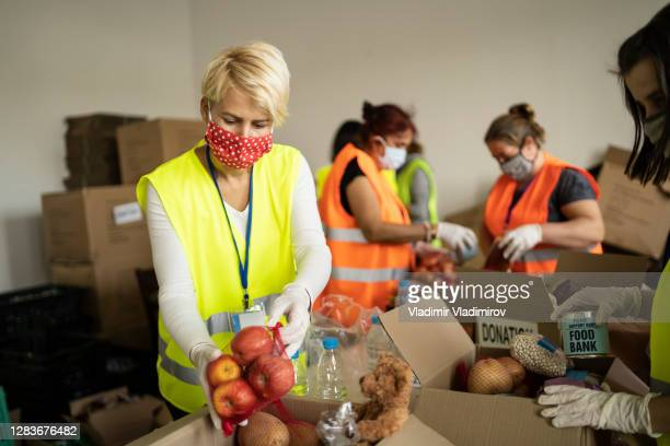 woman with protective face mask helping collecting food in a homeless shelter - humanitarian aid stock pictures, royalty-free photos & images