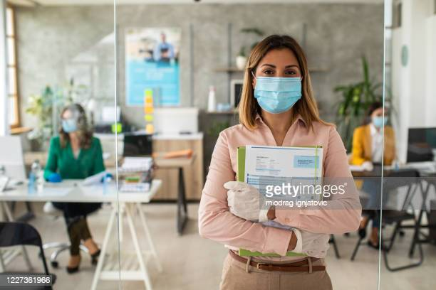 woman with protective face mask in bank office - new normal stock pictures, royalty-free photos & images