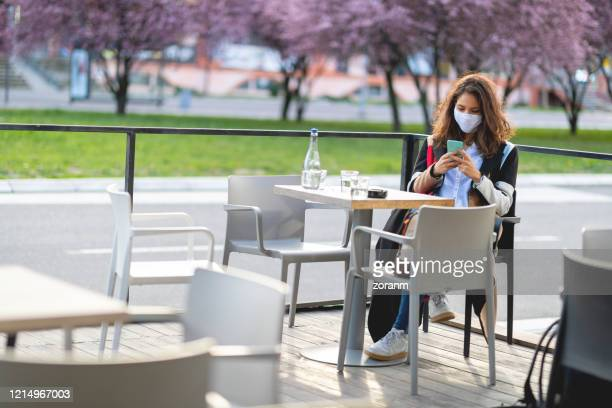 woman with protective face mask in empty cafe - pavement cafe stock pictures, royalty-free photos & images