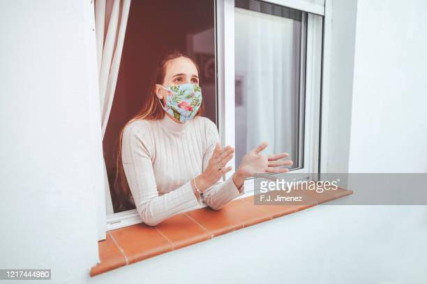 woman with protective mask clapping at the window - aplaudir imagens e fotografias de stock