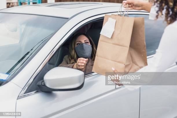 woman with protective mask drives up to get curbside order - drive through stock pictures, royalty-free photos & images