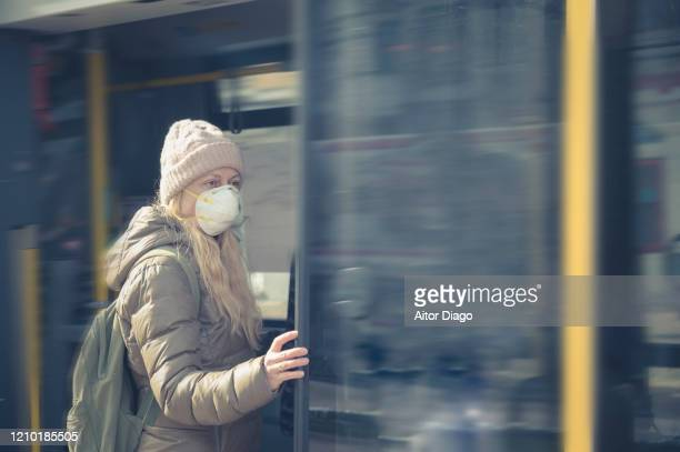 woman with protective mask entering a tram. berlin, germany. - 1918 flu pandemic stock pictures, royalty-free photos & images