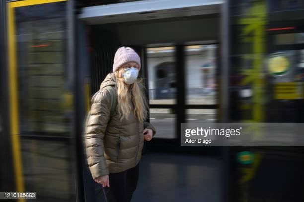 woman with protective mask entering or going out of a tram. berlin, germany. - 1918 flu pandemic stock pictures, royalty-free photos & images