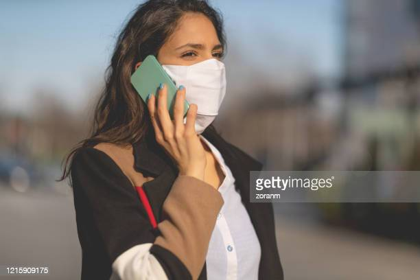 woman with protective mask on the phone - epidemiology stock pictures, royalty-free photos & images