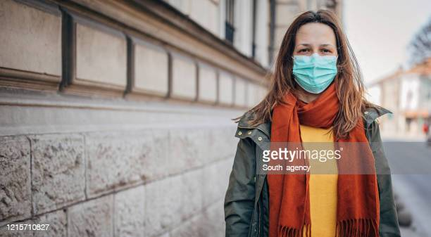 woman with protective mask on the street in city - avoidance stock pictures, royalty-free photos & images
