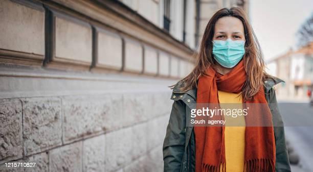 frau mit schutzmaske auf der straße in der stadt - abstand halten infektionsvermeidung stock-fotos und bilder