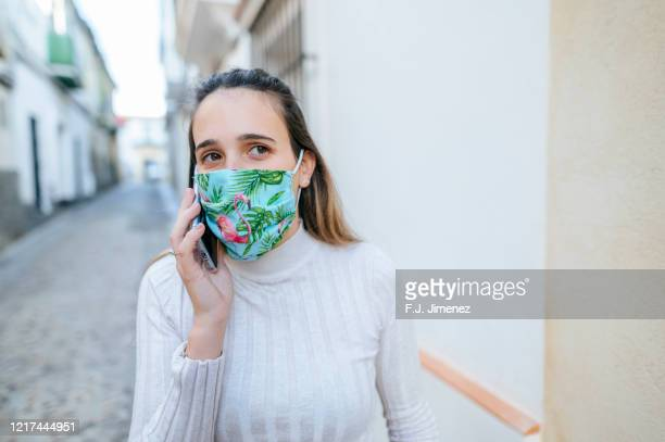 woman with protective mask talking on the phone - face masks imagens e fotografias de stock
