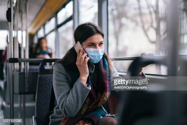 woman with protective mask talking on the phone. - public transportation stock pictures, royalty-free photos & images