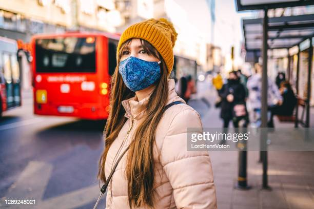 woman with protective mask waiting for the bus - waiting stock pictures, royalty-free photos & images