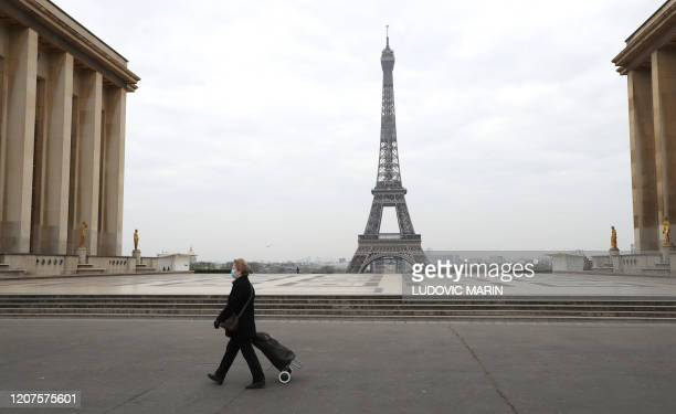 Woman with protective mask walks by the Esplanade du Trocadero square near the Eiffel Tower in Paris, on March 18, 2020 in Paris as a strict lockdown...