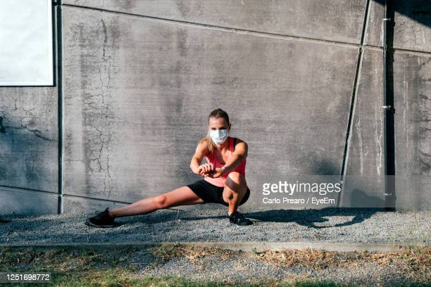 woman with protective mask working out outdoors doing jumping squat against concrete wall background - face guard sport stock pictures, royalty-free photos & images