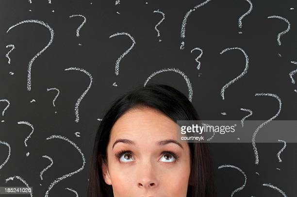 Woman with question marks on a blackboard