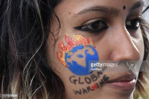 A woman with quotGlobal Warningquot painted on her face participates in a protest against climate change in Mumbai India on 27 September 2019 As they...
