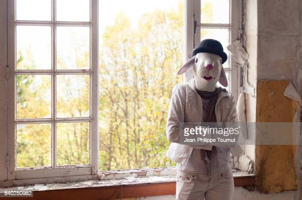 Woman with rabbit mask and bowler hat standing by a window