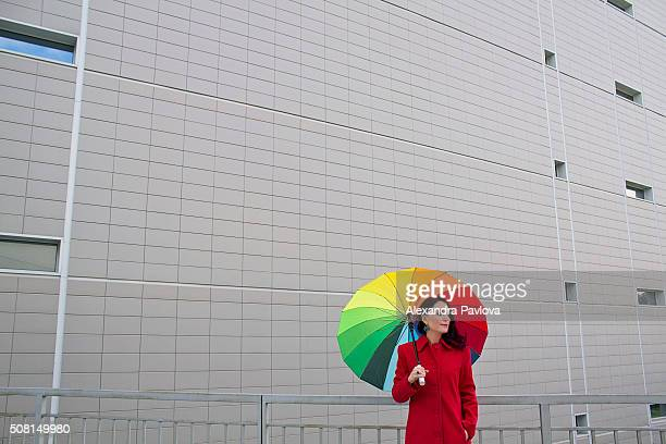 woman with rainbow-colored umbrella standing against grey wall of a building