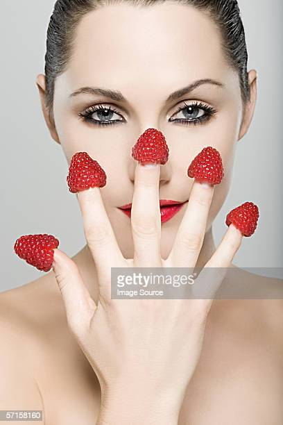 Woman with raspberries on her fingers