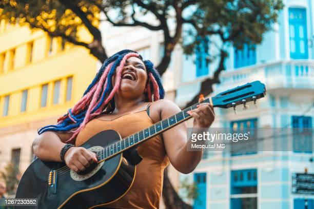 路上でアコースティックギターを弾くラスタファリアンヘアスタイルの女性 - 爪弾く ストックフォトと画像