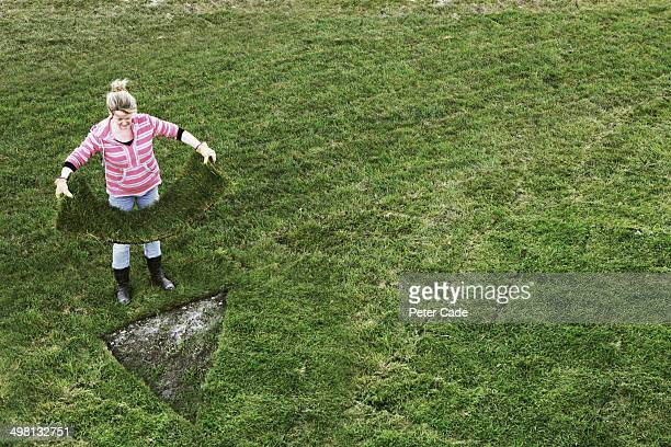 Woman with rectangular turf to lay in triangle gap
