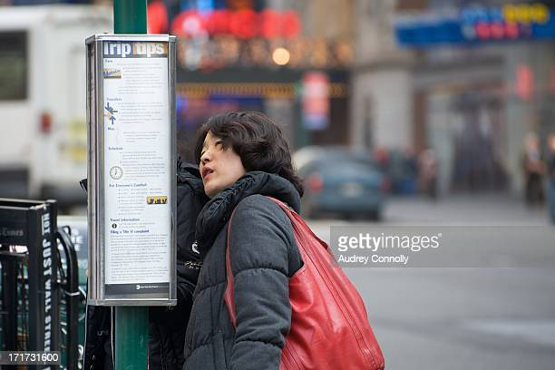 Woman with red bag searching bus schedule in Times Square, New York City