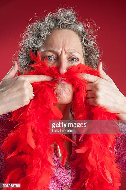 Woman with red boa under her nose as mustache