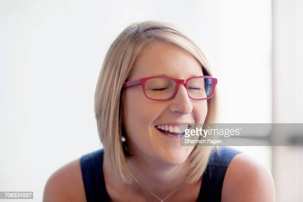 Woman with red glasses laughing in office