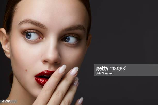 woman with red glossy lips covering her mouth with her hand