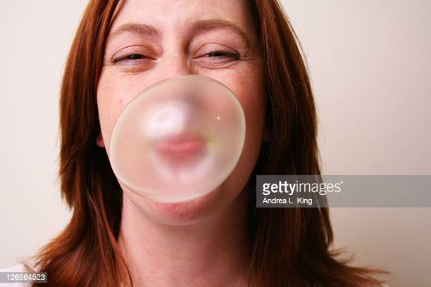 Woman with red hair blowing bubble with gum