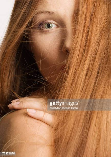 Woman with red hair covering half of face, hand on shoulder, portrait