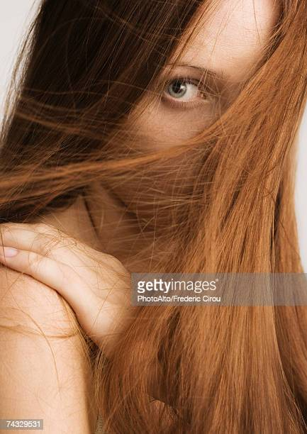 woman with red hair covering half of face, portrait - hair care stock pictures, royalty-free photos & images