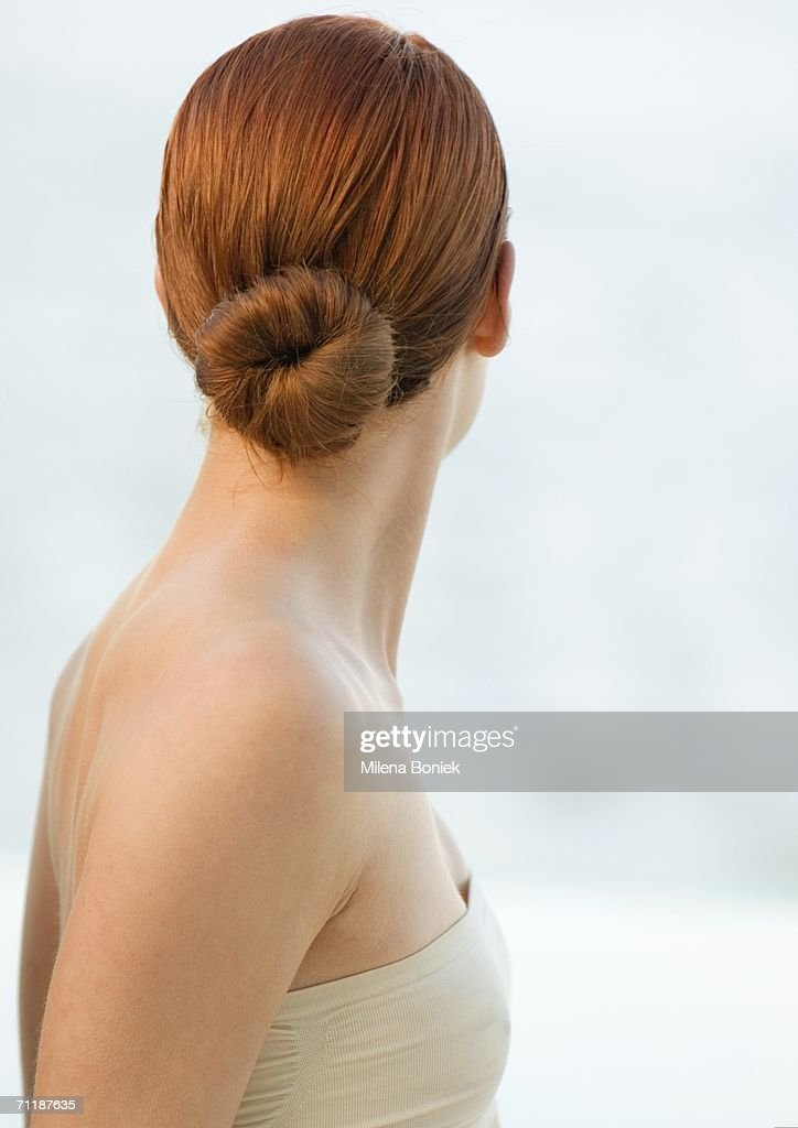 Woman with red hair in bun and strapless top, rear view : Stock Photo