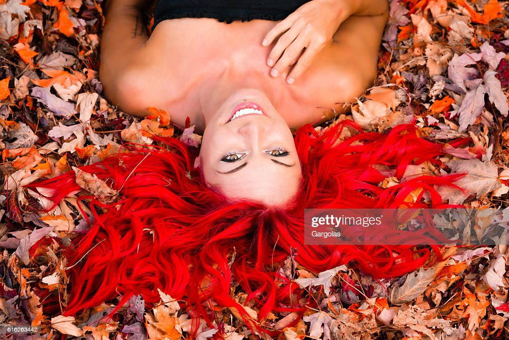 Woman with red hair lying down on colorfull automn leaves : Stock Photo