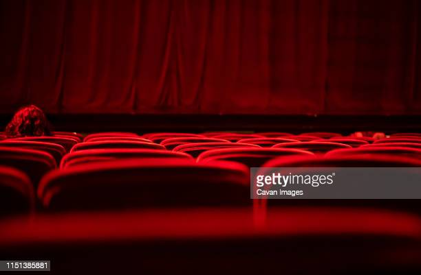 a woman with red hair sitting on a velvet red seat at an empty theater - stage performance space stock pictures, royalty-free photos & images