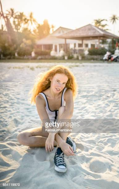 Woman with red hair sitting on the beach