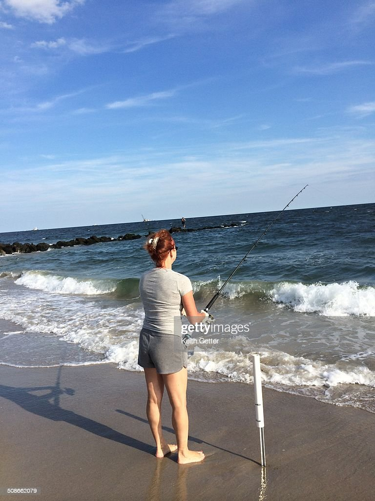 A Woman with Red Hair Wearing Gray Shirt and Shorts is Fishing with a Casting Rod along the shoreline at Ft. Tilden Beach, Gateway National Recreation Area, Rockaway Peninsula , Queens , New York City, USA.