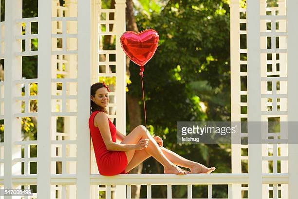 Woman with red heart shape balloon sitting on park bench