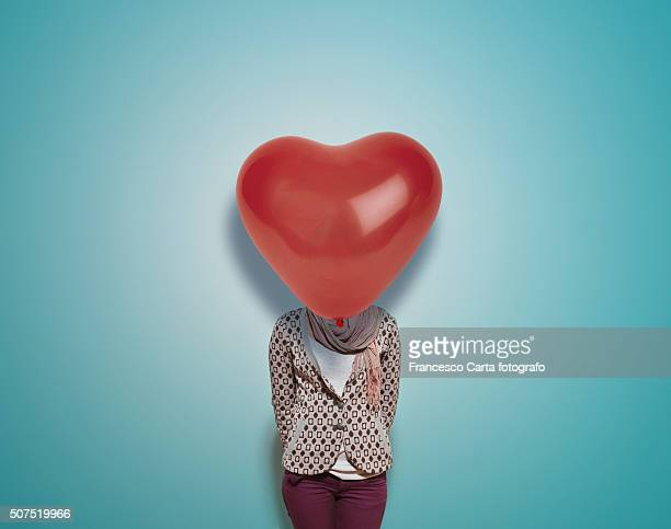 Woman with red heart-shaped balloon