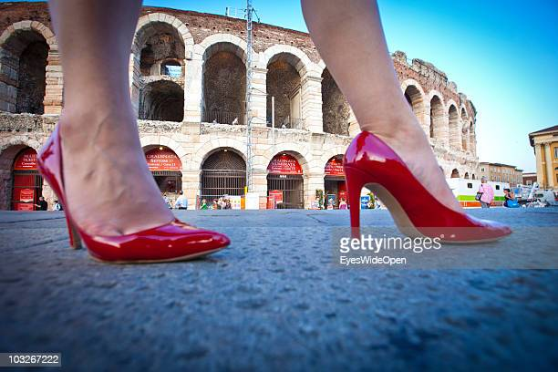 Woman with red high heels in front of the Arena of Verona on July 14, 2010 in Verona, Italy. The famous Arena di Verona is popular for the annual...