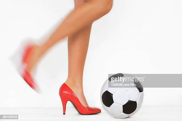 Woman with high heels kicking soccer ball, low section