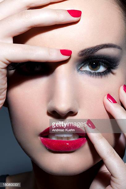 Woman with red lips and nails, close up.