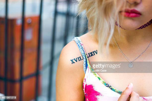 woman with red lips showing tattoo on shoulder