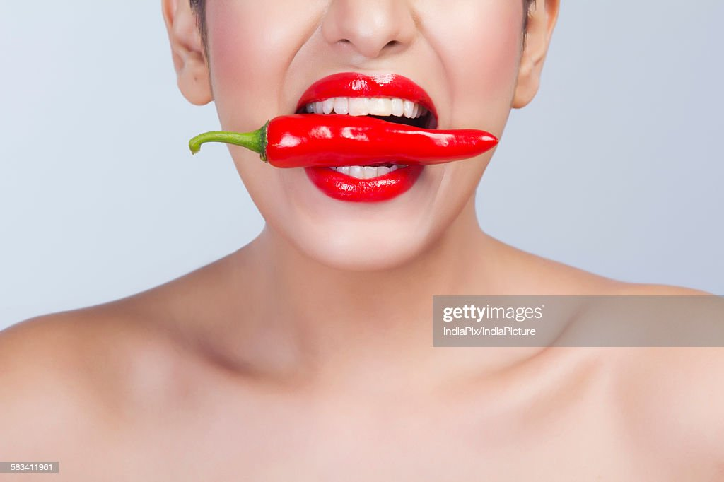 Woman with red pepper between her teeth : Stock Photo